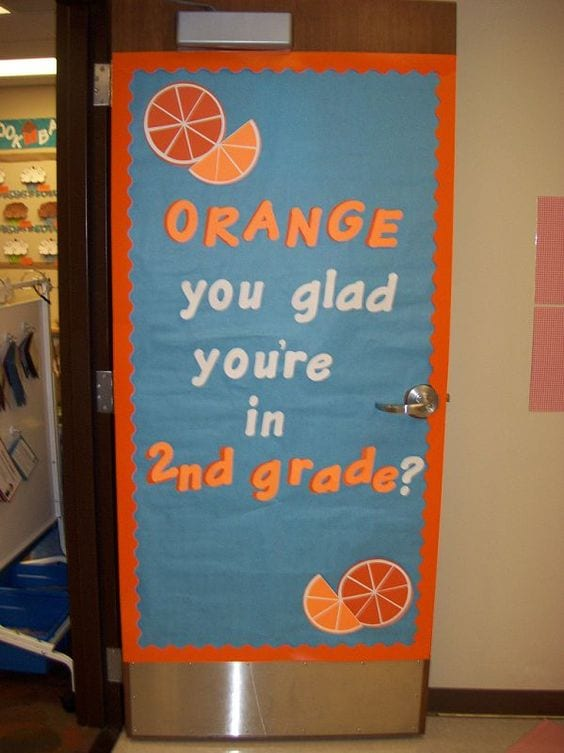 """Door decoration of a blue background and oranges with the words """"Orange you glad you're in 2nd grade?"""" -- classroom doors"""