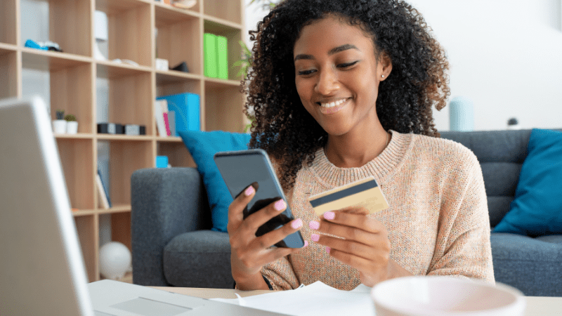 Young woman looking at her credit card and her phone in front of a computer