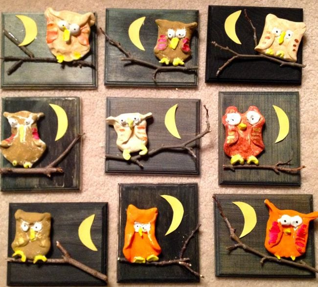 Brown and orange clay owls perched on sticks and mounted on black plaques (First Grade Art)