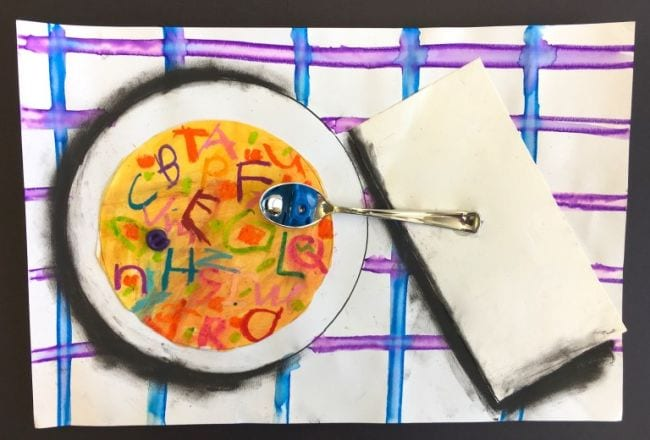 Mixed media art project showing bowl of alphabet soup with a napkin and a real spoon holding an alphabet bead