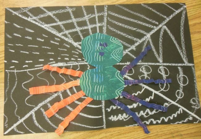 Chalk spiderweb drawn on black construction paper, with patterned paper spider on top (First Grade Art)