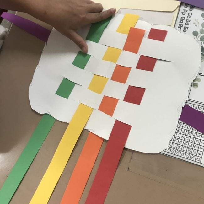 White paper cloud with green, yellow, orange, and red strips woven through it (First Grade Art)
