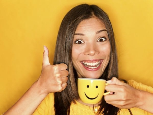woman smiling with a mug and thumbs up