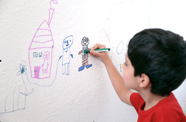 Child writing on walls in classroom