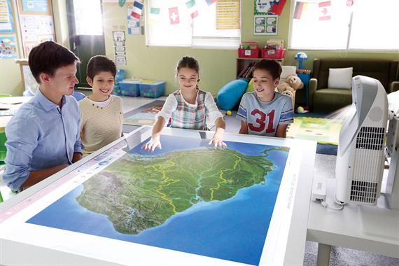 Kids around table with interactive projector in a classroom