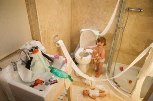 Kids in messy bathroom covered with toilet paper and soap.