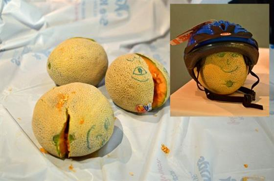 Cantaloupes with faces drawn on them with marker, one wearing a bike helmet