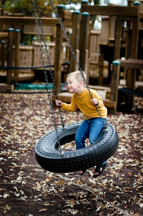 Boy on tire swing on playground.