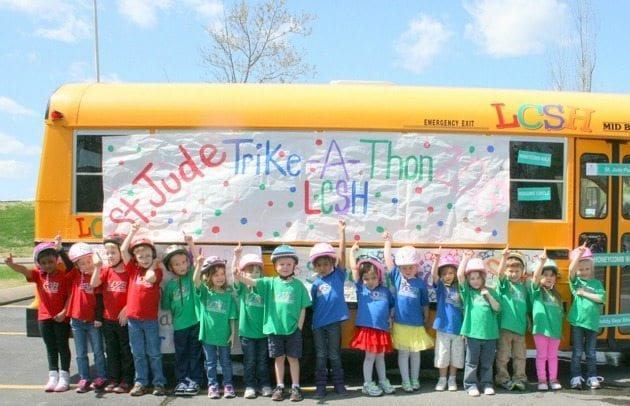 st. jude trike-a-thong event invite community kids in front of school bus