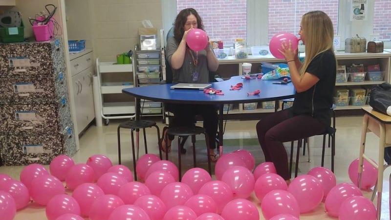 Teachers blowing up pink balloons on classroom floor