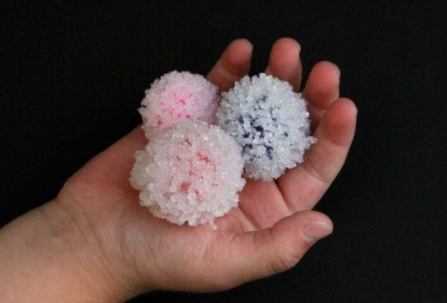 Child's hand holding crystal-covered pom pom balls (2nd Grade Science)