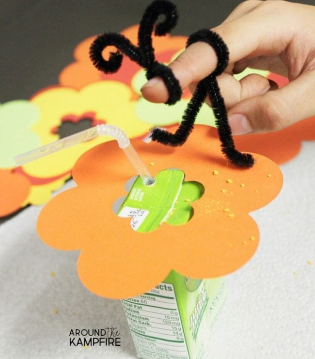 Pipe cleaner twisted into bee shape on a child's finger, sitting on a paper flower (2nd Grade Science)