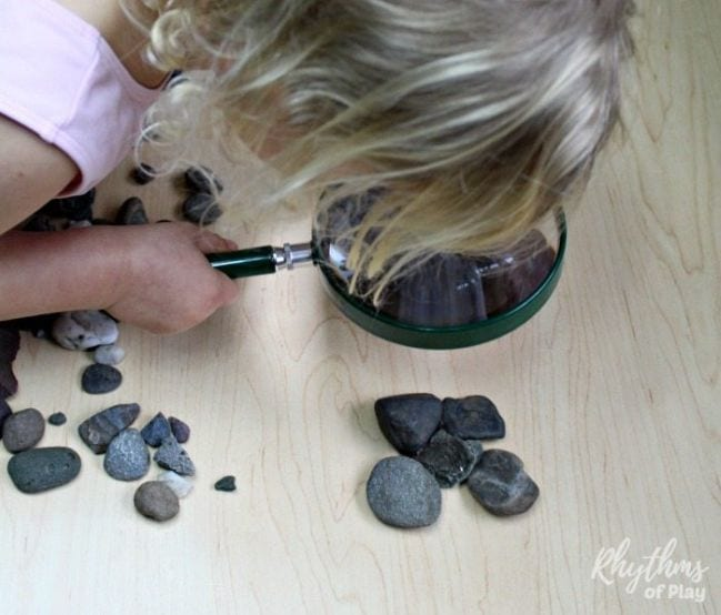 Small child looking at rocks through a magnifying glass