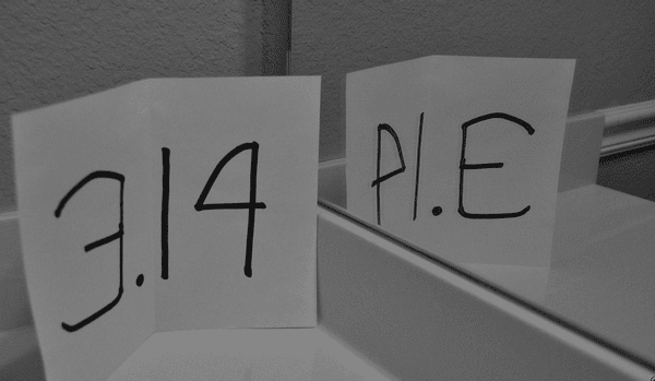 Index card with 3.14 written in black marker propped next to the mirror and showing the reflection as PIE