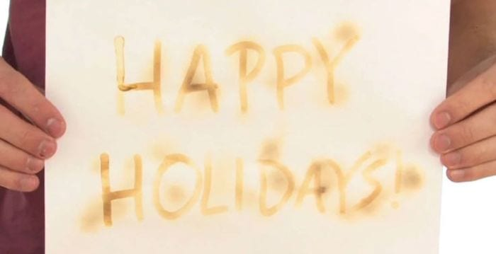 Third grade science student holding paper saying Happy Holidays written in lemon juice