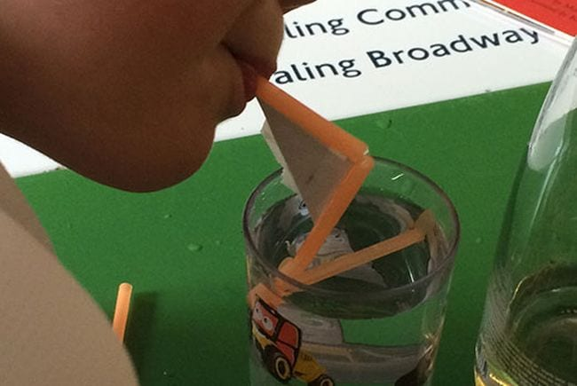 Third grade science students blowing through a straw into a cup of water