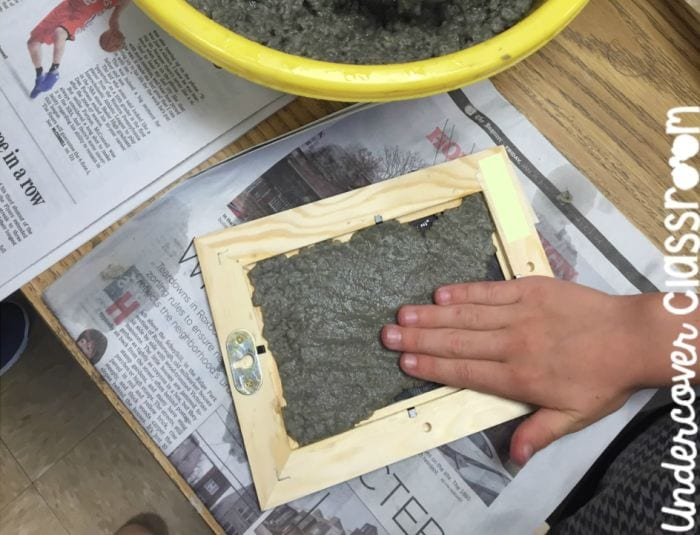 Third grade science student pressing paper pulp into a wood photo frame