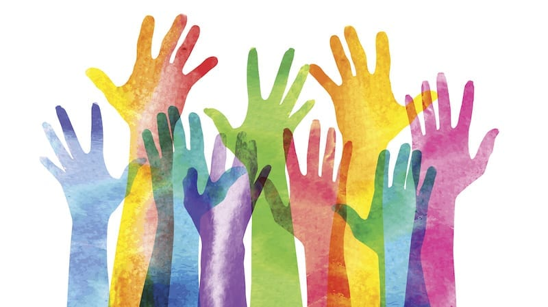 multi-colored painted hands being raised in the air