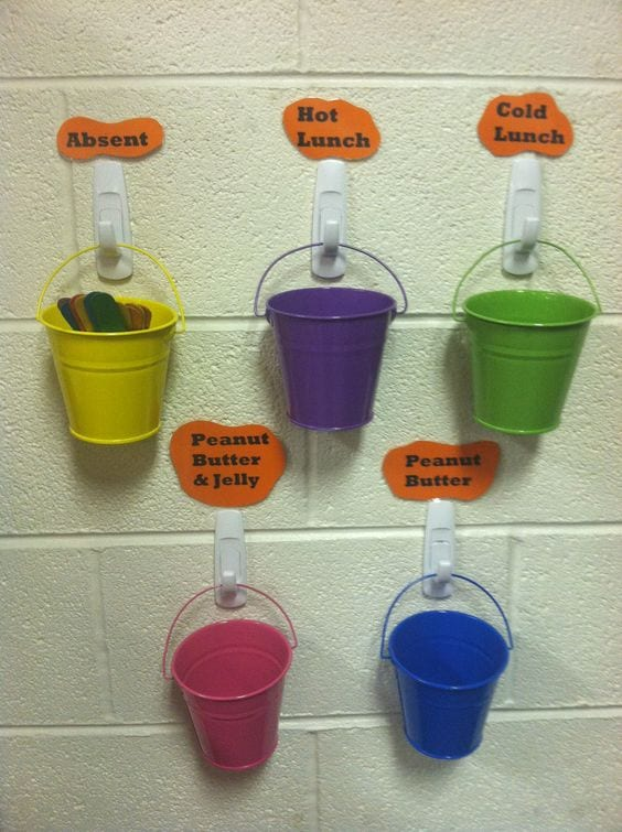 Multicolored buckets hanging on wall on white hooks with lunch options