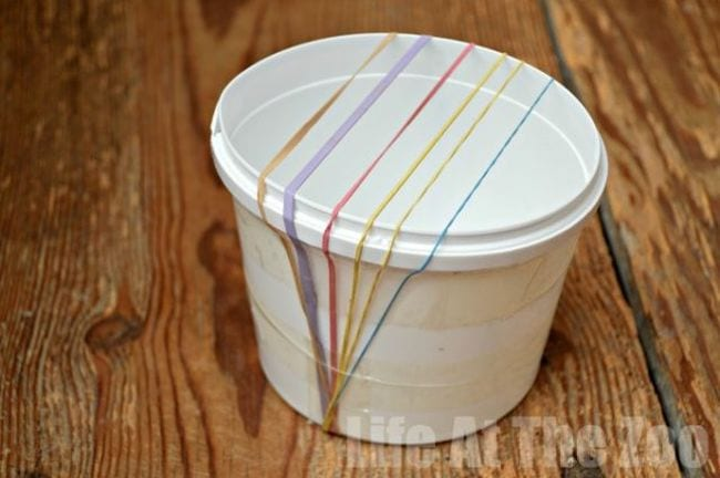 White plastic cup with rubber bands stretched across the opening (Easy Science Experiments)