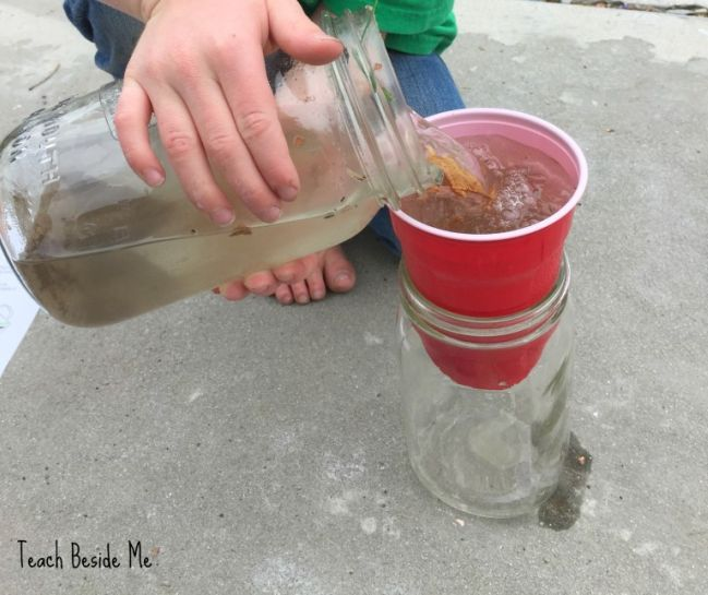 Child pouring dirty water into a cup sitting on top of a large mason jar (Fifth Grade Science)