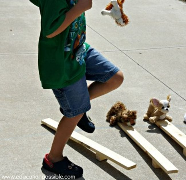 Sixth grade science student stomping on a basic catapult made from a wood block and piece of lumber, sending stuffed animals flying