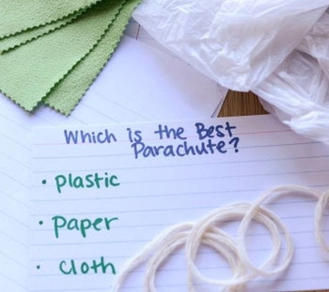 Card with text Which is the best parachute? Plastic, paper, cloth. Surrounded by pieces of fabric, plastic, and string.