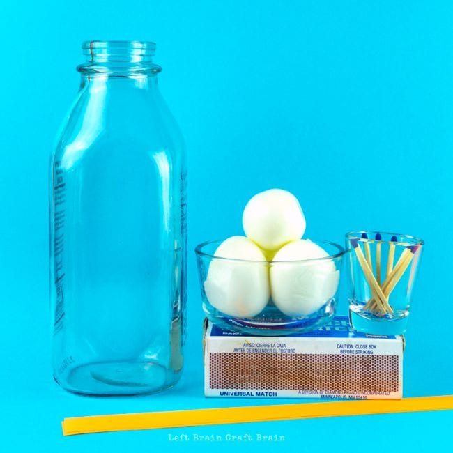 Empty bottle next to a bowl of eggs and a cup of matches with a plastic straw (Easy Science Experiments)