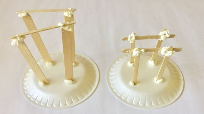 Two foam plates with structures built from wood craft sticks and putty on top