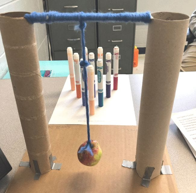 Wrecking ball made from an apple suspended from a rod between two upright paper towel tubes, aimed at an arrangement of markers