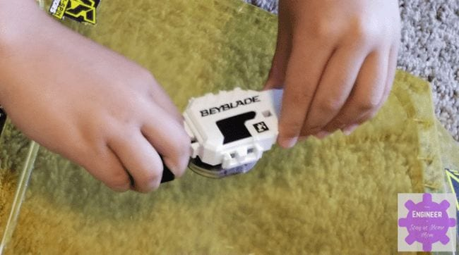 Student's hands holding a white Beyblade top (Seventh Grade Science)
