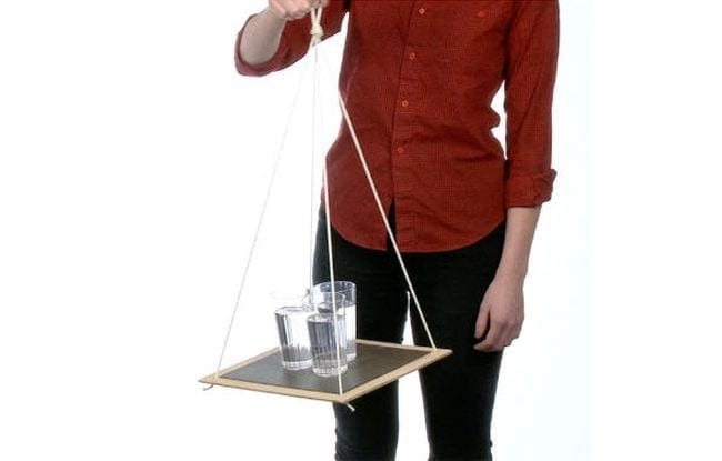 Teacher holding a platform swing from four strings with three glasses of water on it