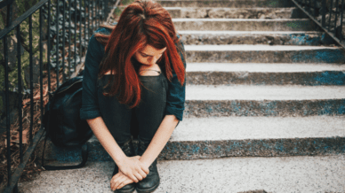 depressed teen girl sitting on steps outside