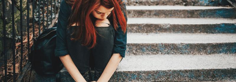 depressed teen girl sitting on steps outside
