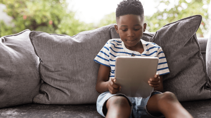 young boy sitting on sofa reading on tablet - teaching reading remotely