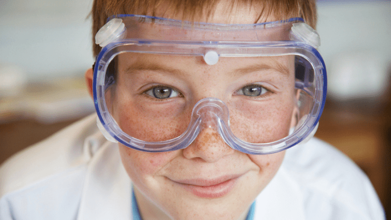 close up of boy wearing lab coat and goggles