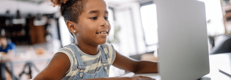Elementary school girl on laptop, smiling.