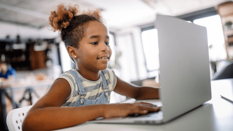 Elementary school girl on laptop, smiling.