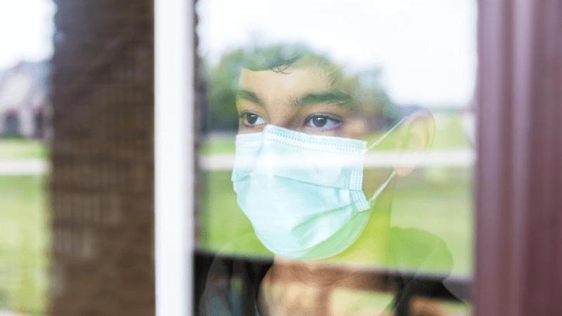 Sad teen boy wearing mask gazing out window.