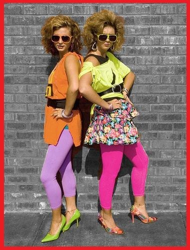 Two girls wearing bright 80's style clothing -- teaching a long time