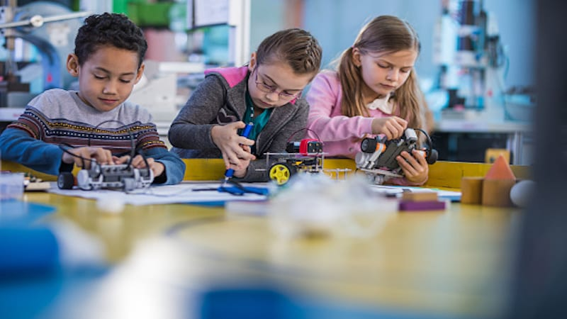 Three young students working on STEM projects at table in classroom