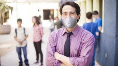 A school principal wearing a mask and looking at the camera.