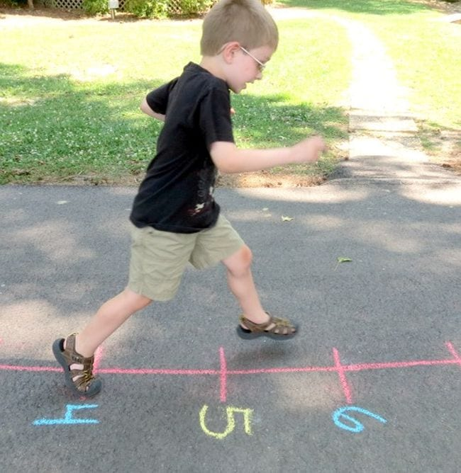 Young student running along a number line drawn on the sidewalk