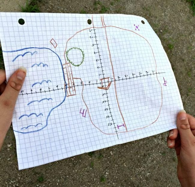 Student holding a piece of graph paper with a map drawn on it
