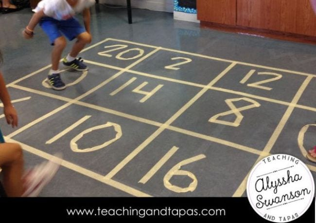 Student jumping on a large number grid made of masking tape on the floor (Active Math Games)
