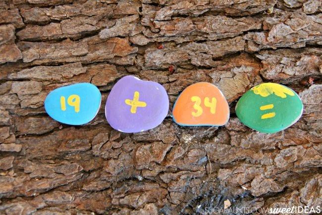 Colorful rocks painted with 19, plus sign, 34, and equals sign