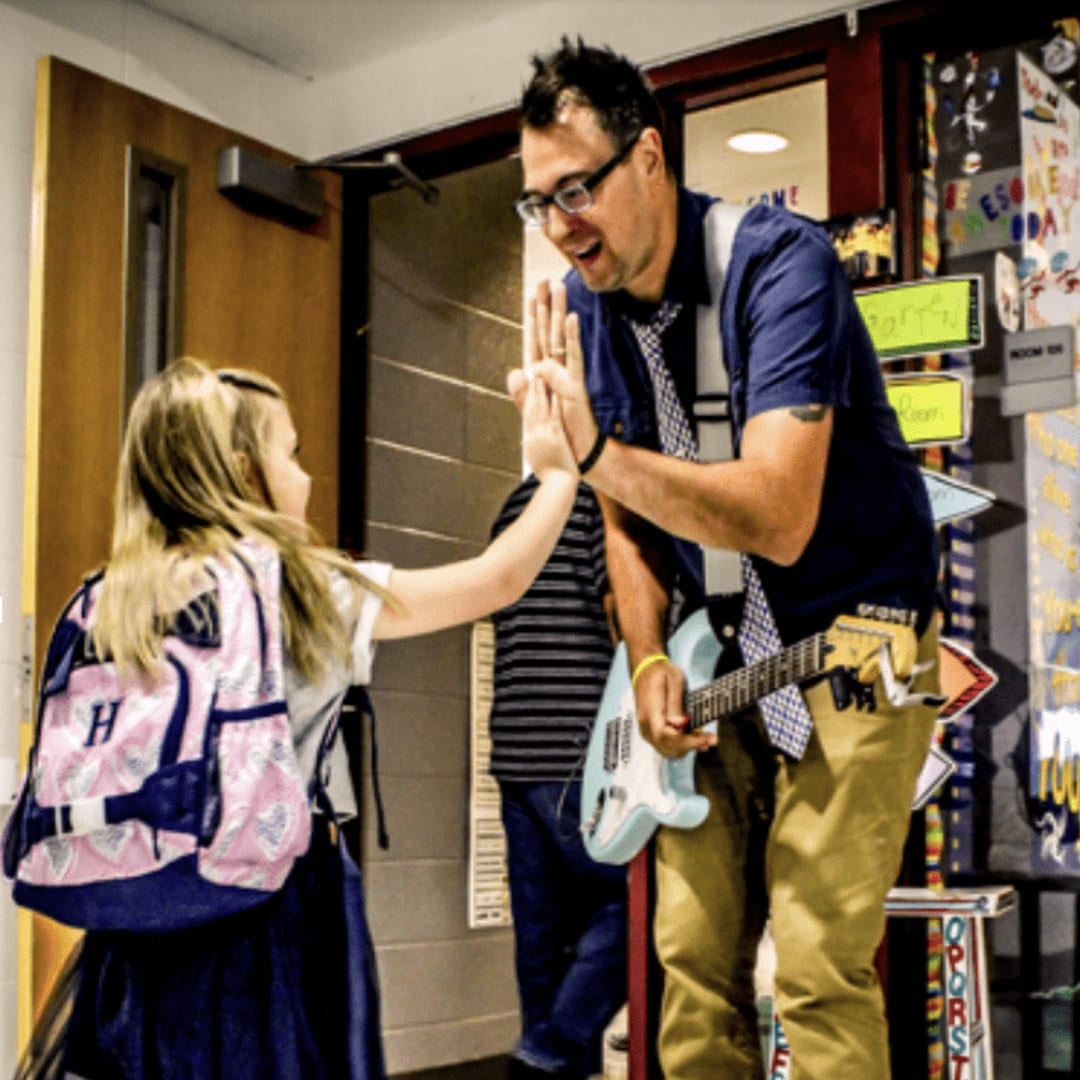 Adam greeting his student so she has the BEST day ever at school.