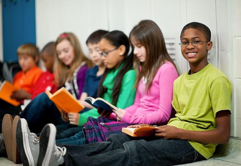 Kids reading books in hallway -- Volunteer Projects Help Teens
