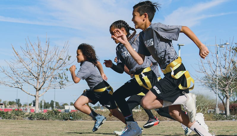 Three elementary school students playing flag football with the NFL Flag In Schools Kit at schools.