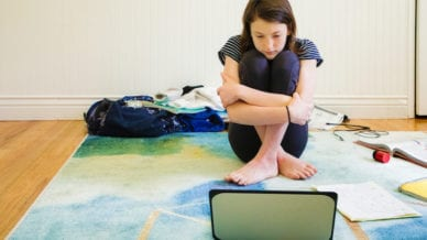 Sad female teenager watching media on laptop hugging herself sitting on the carpet with homework material and clothing around her.